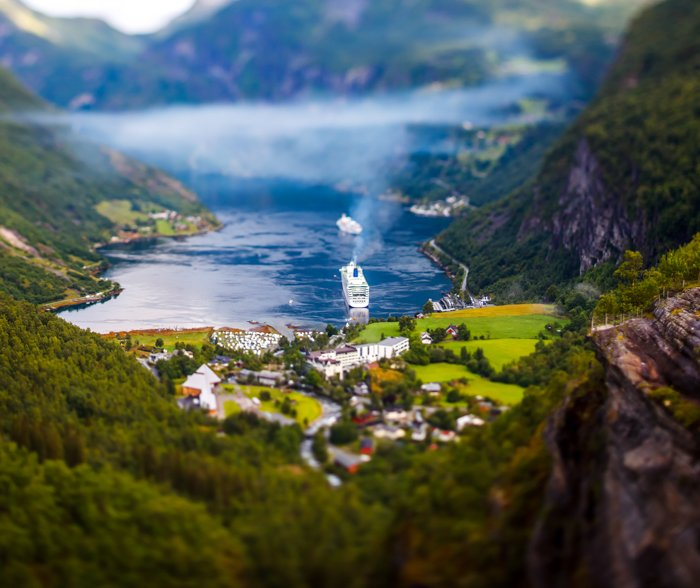 a tilt shift image of a boat setting out on the water within a valley