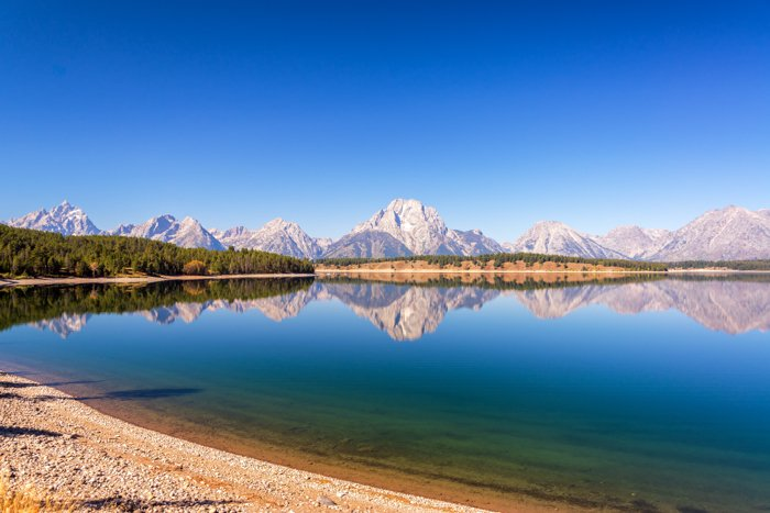 Wide angle view of the Teton Range reflected in Jackson Lake in Grand Teton National Park Wyoming