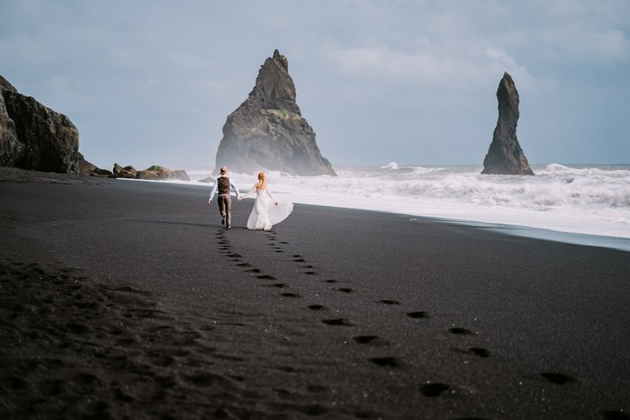 an image of a married couple walking hand in hand on a black sand beach