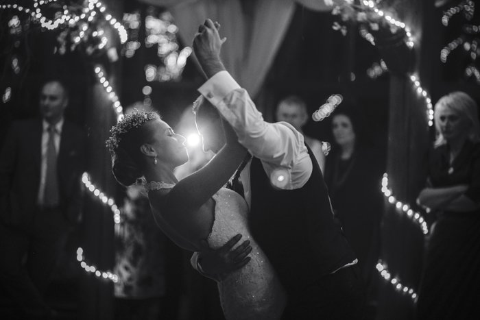 a black and white image of a newly married couple dancing