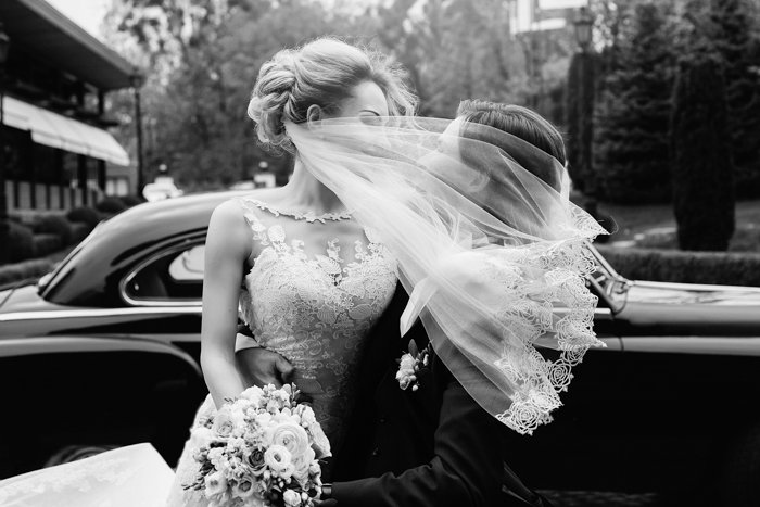a black and white image of a bride sitting on a groom's lap in front of a classic car