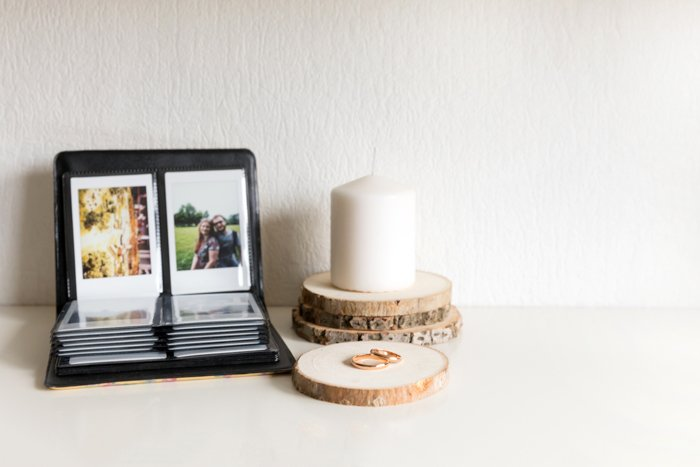 an analogue image of a instant photo album set next to a candle