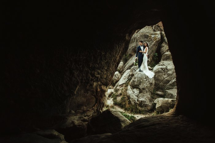 a wedding photograph of a couple standing outside the entrance of a cave