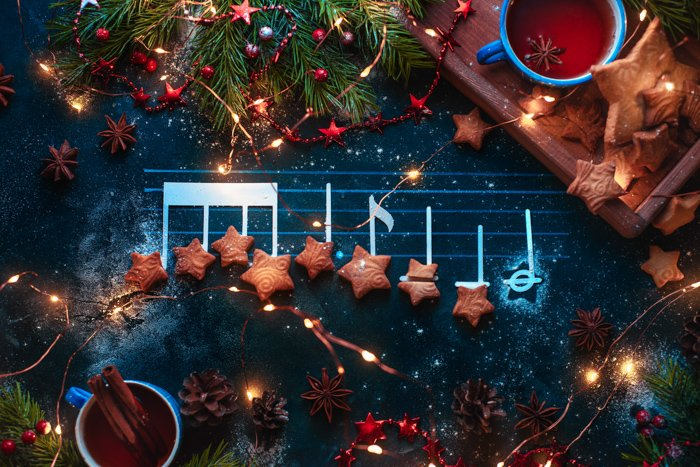 Christmas melody notes flat lay with star-shaped cookies, fir tree branches, wooden tray, anise stars, and decorations.
