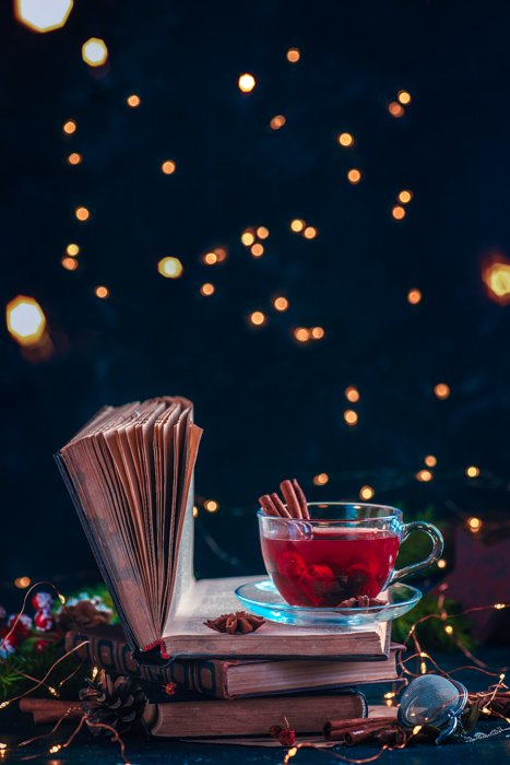 Redberry tea on a stack of books with fairy lights. Christmas drink on a dark background with copy space