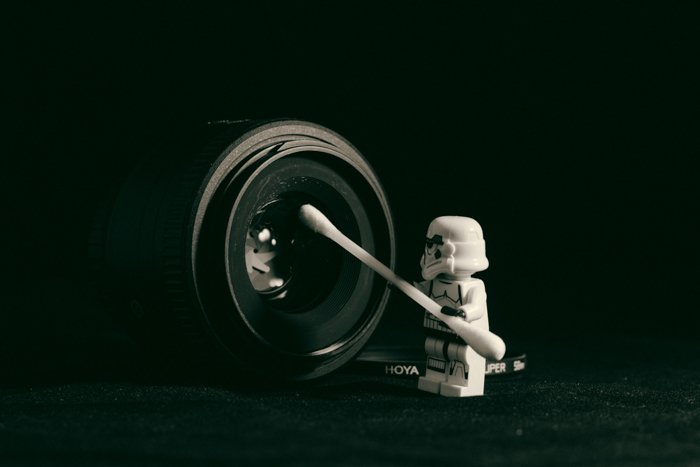 A lego figure cleaning a camera lens