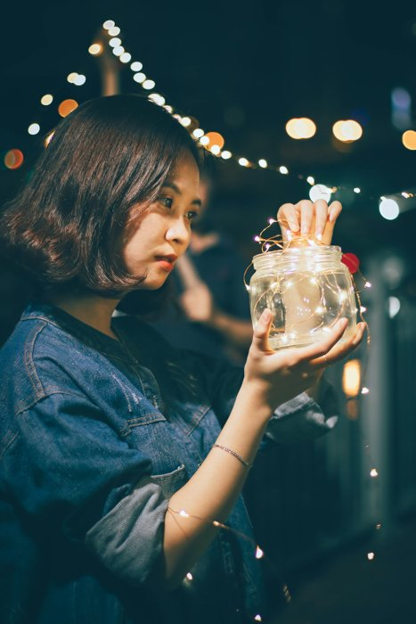 Personalized Christmas card photo of a girl putting fairy lights into a jar