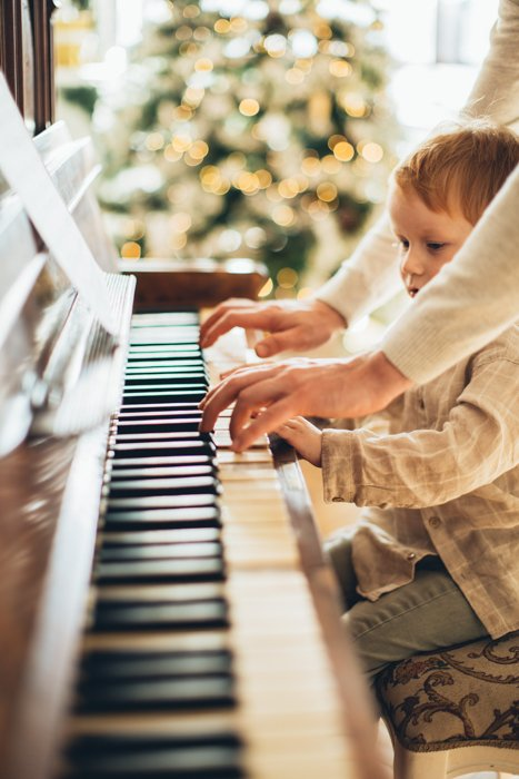 Personalized Christmas card photo of a child and parent playing piano together