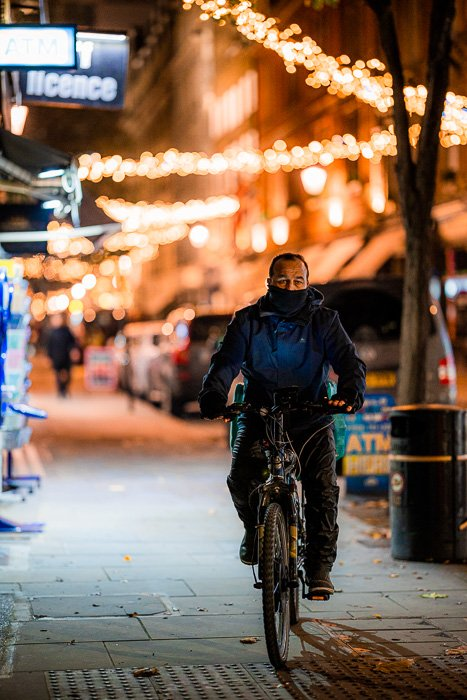Street photography of a cyclist on the street taken with the Canon RF 85mm