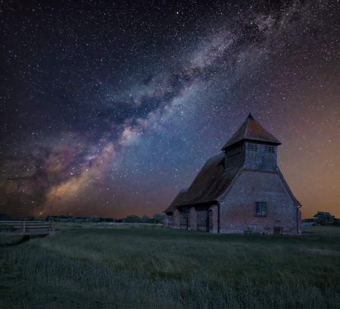 Image of the Milky Way behind a landscape with an old building
