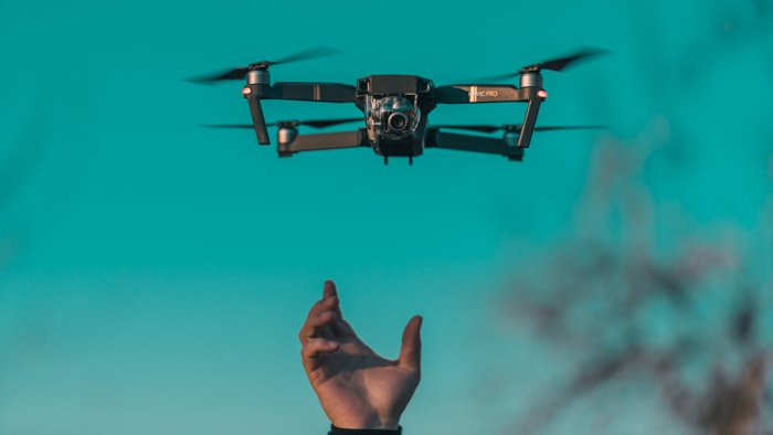 A hand releasing a drone