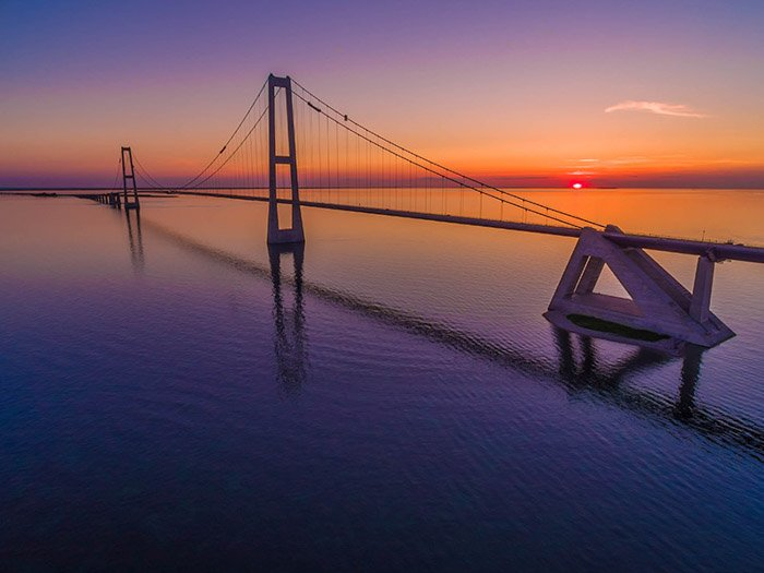 a drone photography image of a bridge across water at sunset
