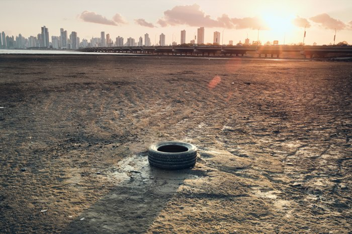 A documentary image of a rubber tyre on parched soil against an urban skyline