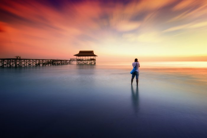 Long exposure photo of a photographer on a beach at evening time