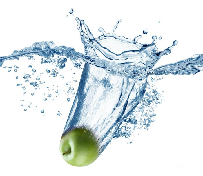 Green apple falls deeply under water with a big splash.