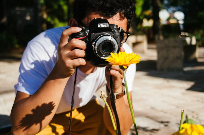 A man taking a photo of a flower