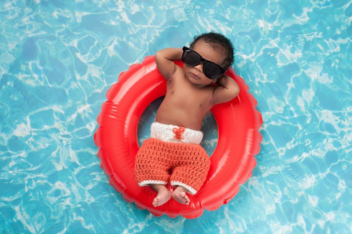 Funny newborn photography idea of a baby posed in sunglasses on a rubber ring in a pool