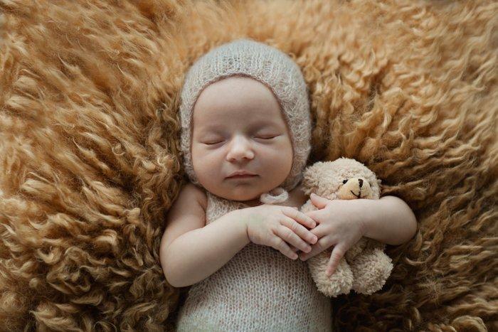 Sweet portrait of a newborn baby holding a teddy bear