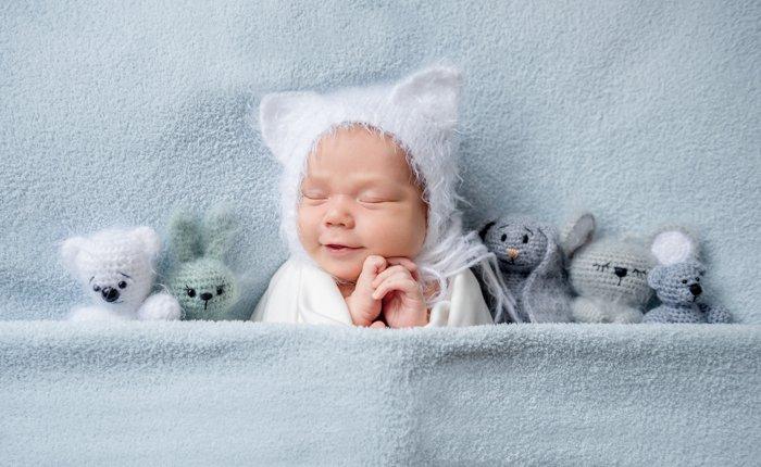 Sweet portrait of a newborn baby in bead with teddy bears