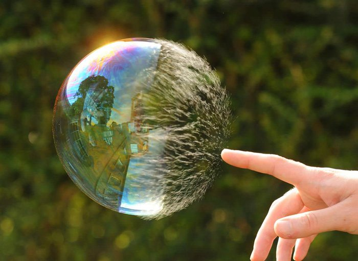 A person touching a huge bubble