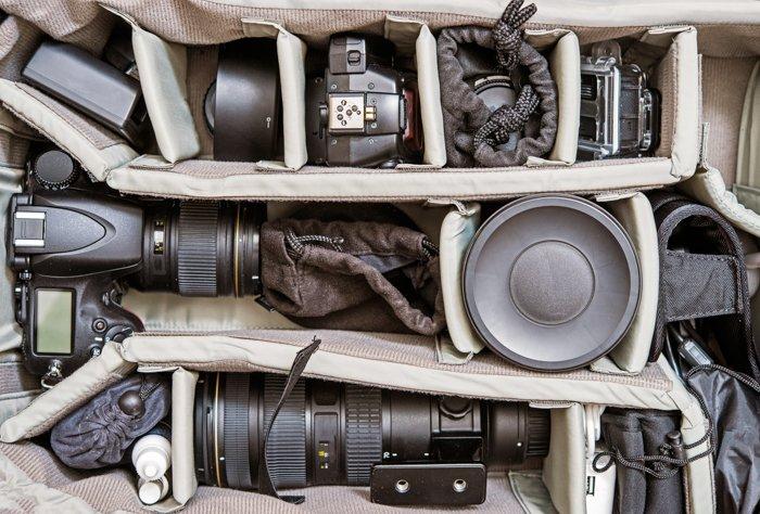 A picture of photography gadgets and photography equipment in a photo bag.