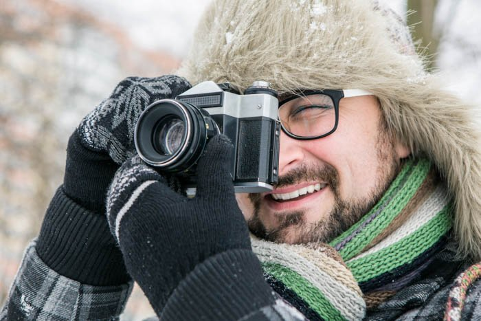 Guy taking a photo in winter while wearing outdoor photography gloves