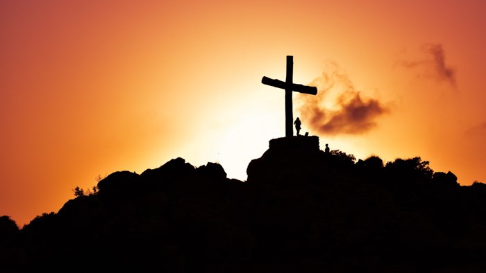 Cool silhouette photography of a girl beside a giant cross on a mountain at sunset