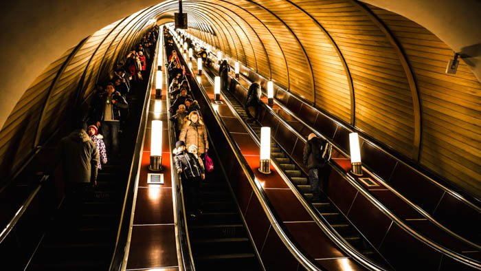 Deep subway station is crowded with people riding the escalators
