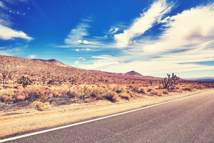 A saturated image of a road and the desert behind it