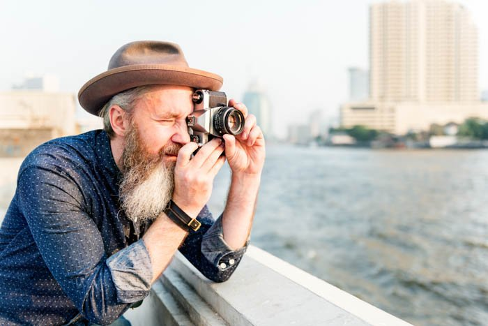 An image of an old traveller taking a picture with film camera