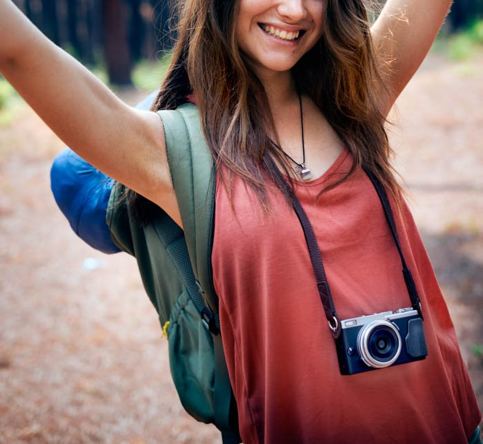 A young travel photographer posing with her camera