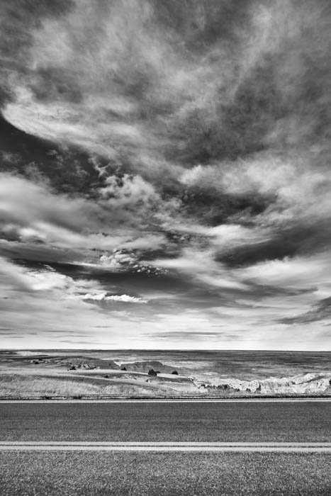 A black and white photography of a road and the clouds