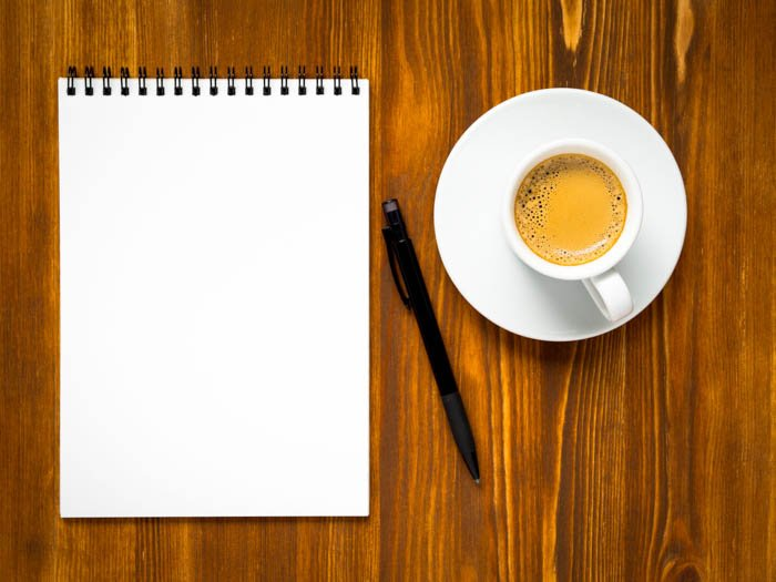 Notepad open with blank page for writing travel to-do list, a Cup of coffee and pen on the wooden brown table