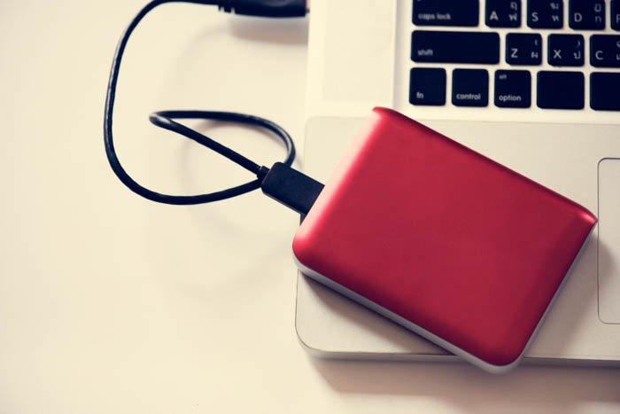An external hard drive placed on a laptop.