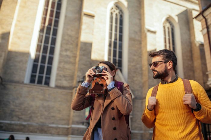 A travel photographer taking an architectural photograph beside her boyfriend