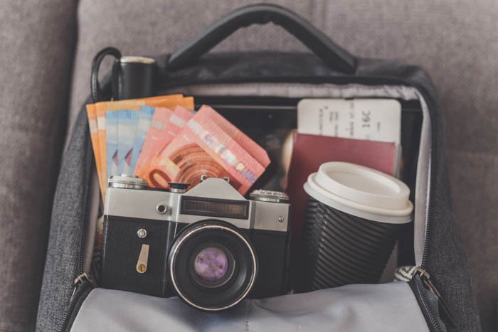 Opened backpack with things needed for travel photography like camera, money, passport and tickets