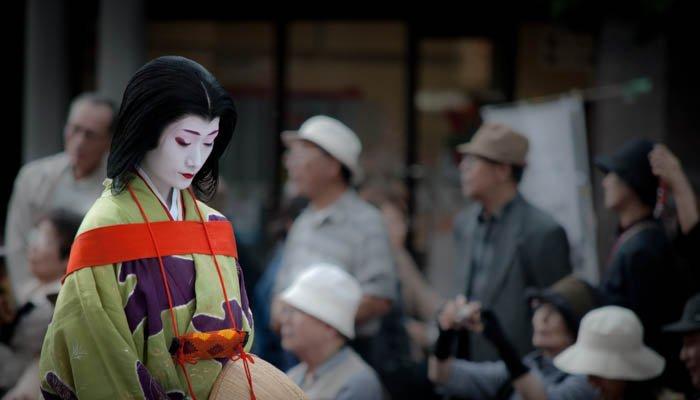 A street photo of a Japanese women wearing geisha attire