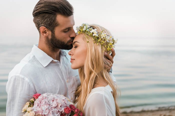 A groom giving a kiss onto the bride's forehead