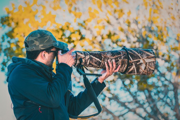 A photographer holding a telephoto lens in nature