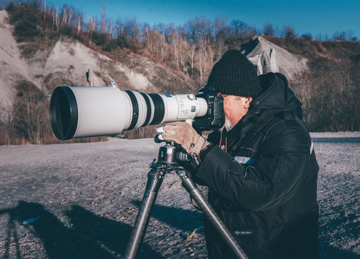 A wildlife photographer shooting with a super telephoto zoom lens