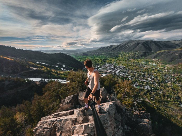 adventure photography of a man with a gopro on a stick looking out toward a valley