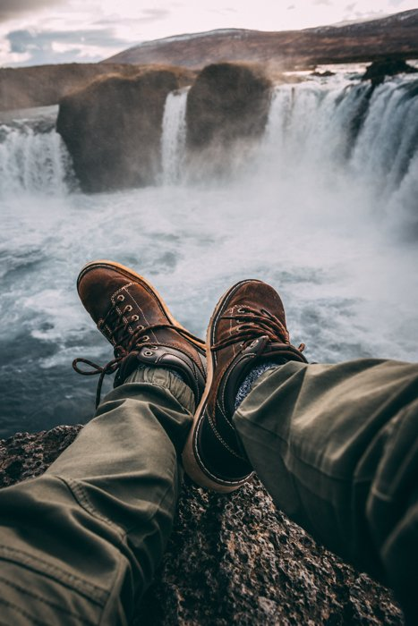 a closeup image of a mans legs and shows against a large waterfall