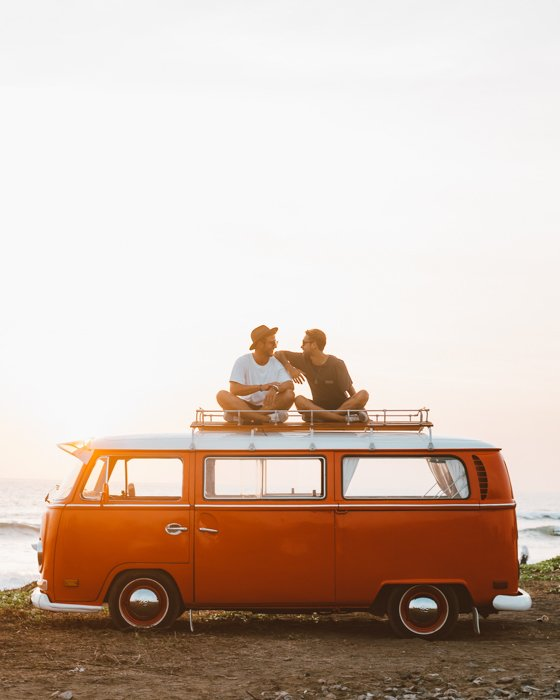 an image of two friends sitting on top of an orange volkswagen bus