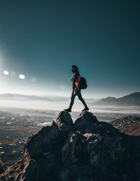 an image of a man standing at the summit of a mountain