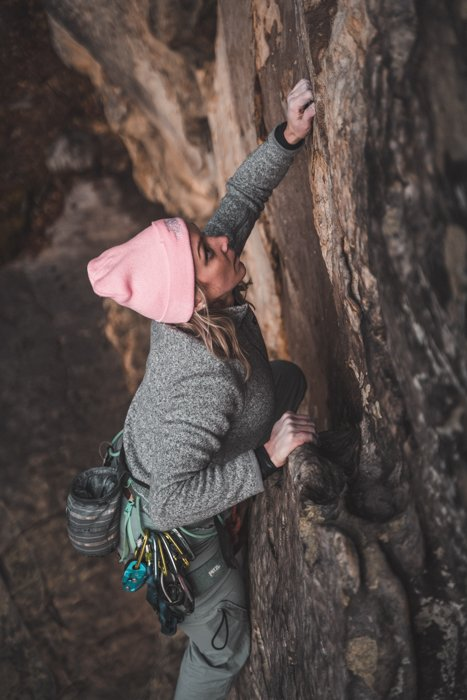 adventure photography of a woman in a pink hat climbing up the side of a mountain