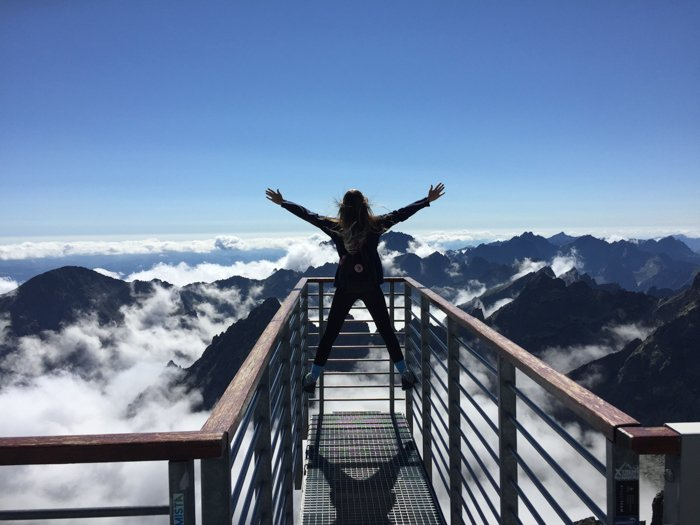 an image of a woman at the summit of a mountain looking beyond the clouds