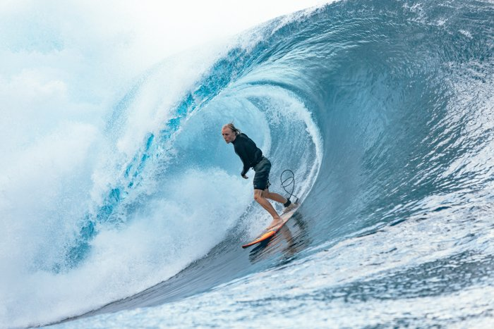 adventure photography of  a surfer riding a blue wave