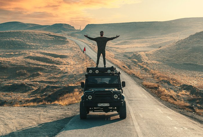 adventure photography of a man standing on top of a truck while driving through the desert