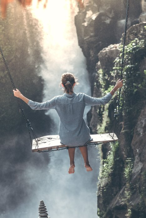 an image of a woman swinging above a ravine