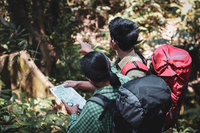 an image of two men in the jungle looking at a map
